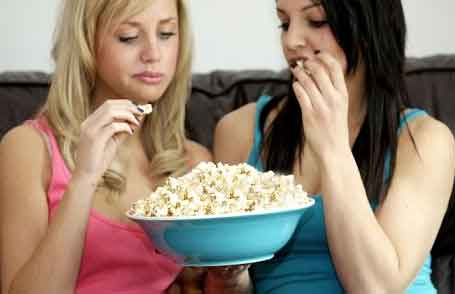 Girls eating Popcorns in Theatre